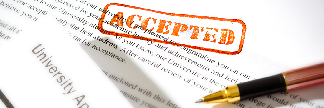 "An acceptance letter from a university application. An university application form together with the letter of acceptance with a red rubber stamp of ""Accepted"" on a table top still life. Photographed close-up in horizontal format with selected focus on the rubber stamp impression."